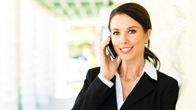 Une femme agent immobilier au téléphone dans un couloir ensoleillé