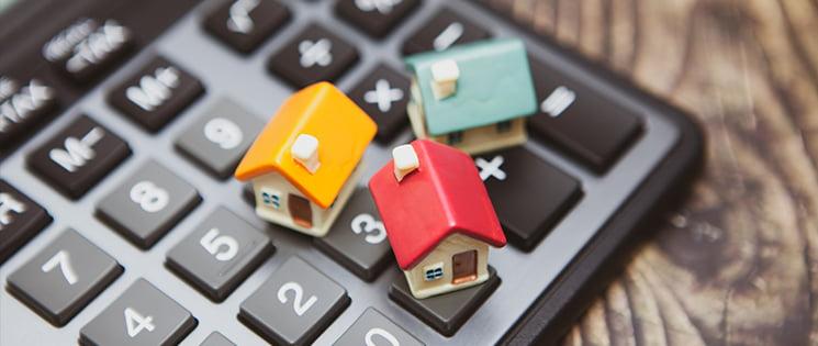 Trois maisons en miniature céramique de couleurs différentes : jaune, rouge et bleu ciel. Elles sont posées sur les touches d'une calculatrice