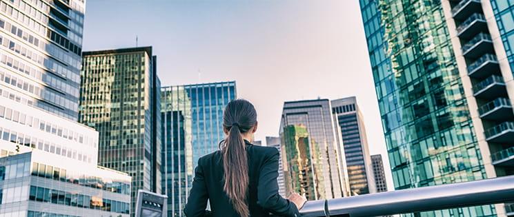 une femme vêtue d'une veste de bureau regarde des immeubles de bureaux.